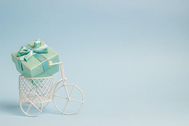 Zabawkowy rower nosi prezent. pomysł na pocztówkę. niebieski . minimalizm.