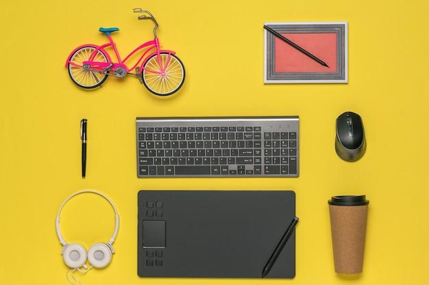 Zabawkowy rower, obrazek, klawiatura i tablet graficzny na żółtym tle. miejsce pracy projektanta.