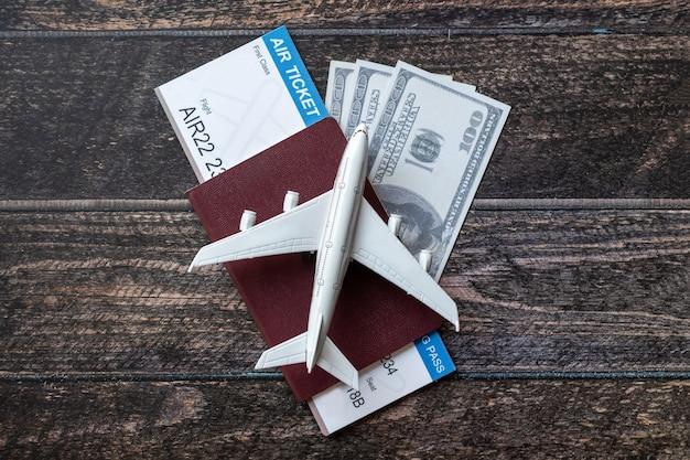 Zabawkowy samolot, bilet lotniczy, karty kredytowe, dolary i paszport na drewnianym stole. koncepcja podróży