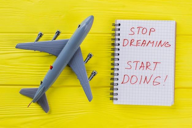 Zabawkowy samolot pasażerski i notatnik z cytatem motywacji. żółty drewniany stół na tle.