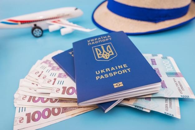 Zabawkowy samolot z ukraińskimi paszportami i hrywnami na niebiesko. pojęcie turystyki, podróże.