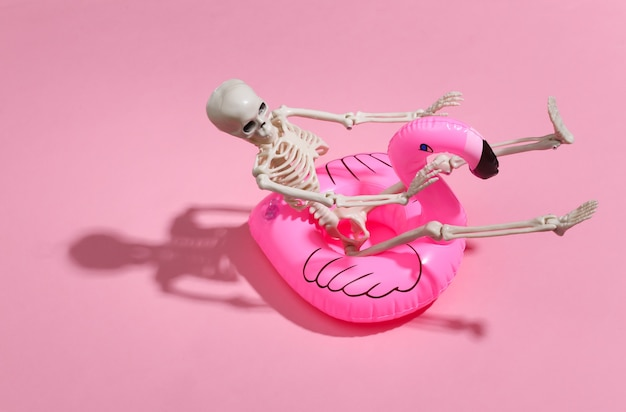 Zabawkowy szkielet z dmuchanym flamingiem na różowym jasnym. motyw halloween. koncepcja wakacje na plaży. letni odpoczynek.