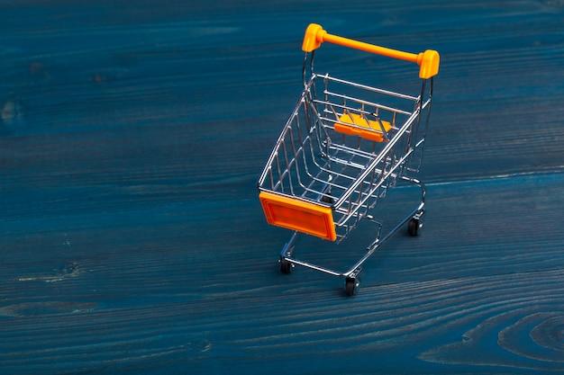 Zabawkowy wózek na zakupy na błękitnym drewnianym stole