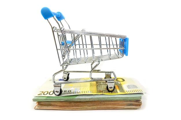 Zabawkowy wózek na zakupy na stosie banknotów euro na białym tle