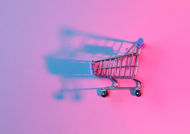 Zabawkowy wózek na zakupy z neonowo różowym niebieskim światłem.