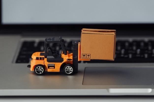 Zabawkowy wózek widłowy z pudełkiem na klawiaturze. koncepcja logistyki i sprzedaży hurtowej