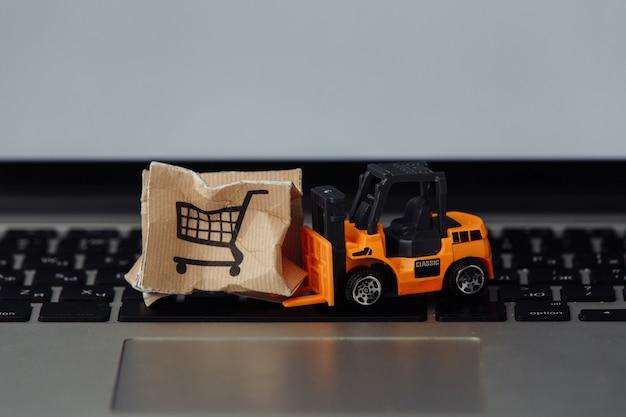 Zabawkowy wózek widłowy z pudełkiem na laptopie. koncepcja logistyki i sprzedaży hurtowej