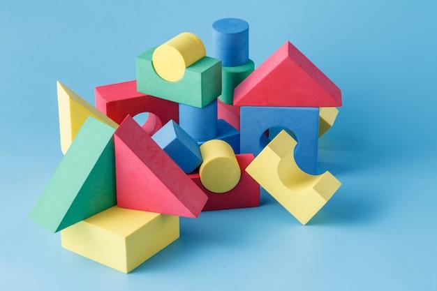 Zabawkowy zamek z kolorowych bloków na niebieskiej powierzchni
