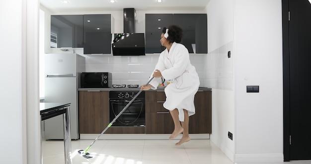 Zabawna afroamerykańska młoda kobieta w białej szacie z mopkiem tańcząca w kuchni