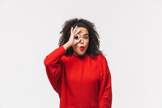 Zabawna afrykańska kobieta w czerwonym swetrze pokazującym znak ok i patrząca bezpośrednio na szarym tle