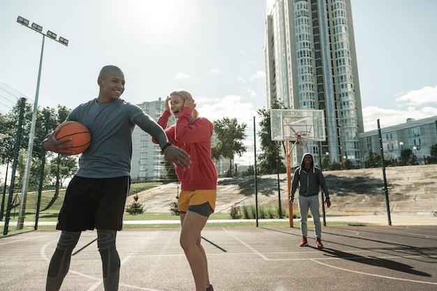 Zabawna aktywność. radosna młodzież, która razem bawi się grając w koszykówkę
