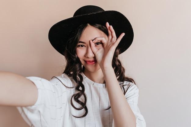 Zabawna azjatykcia kobieta pozuje z ok znak. japoński model w kapeluszu przy selfie na beżowym tle.