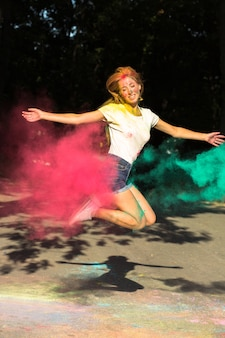 Zabawna blondynka skacze z żywymi kolorami eksplodującymi wokół niej