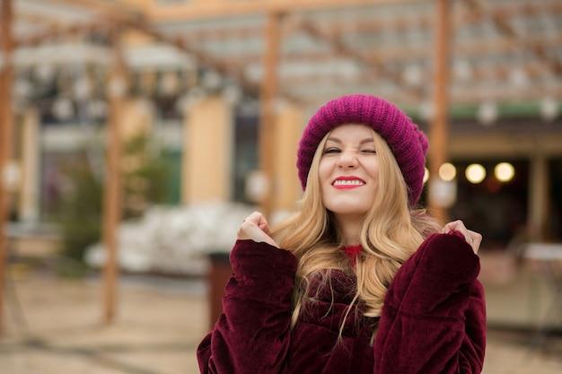 Zabawna blondynka w czerwonej czapce i płaszczu zimowym, pozuje na tle girlandy na ulicy w kijowie