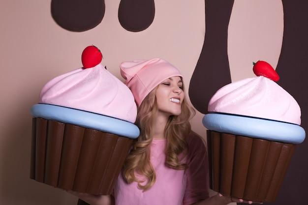Zabawna blondynka w różowej czapce, ciesząc się dużymi babeczkami w studio