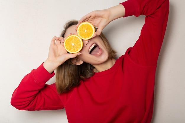 Zabawna brunetka kobieta pozuje z połową pomarańczy, zasłaniając oczy pomarańczą na białej ścianie