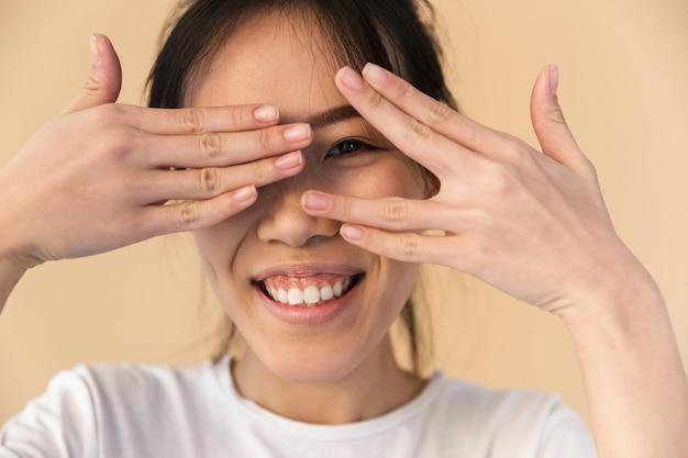 Zabawna chinka ubrana w prosty t-shirt zakrywający oczy i zerkający na beżową ścianę w studio