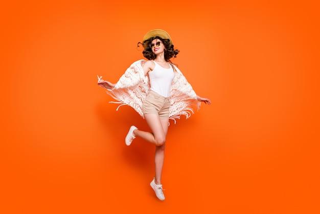 Zabawna dama latem skacząca wysoko, ciesz się wspaniałymi widokami na kurort, noś stylową czapkę przeciwsłoneczną stylowe białe koronkowe szorty plażowe.