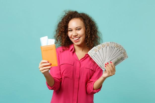 Zabawna dziewczyna afryki trzymać bilet na kartę pokładową paszport, fan pieniędzy w banknoty dolarowe pieniądze na białym tle na niebieskim tle turkus. koncepcja życia szczere emocje ludzi. makieta miejsca na kopię.