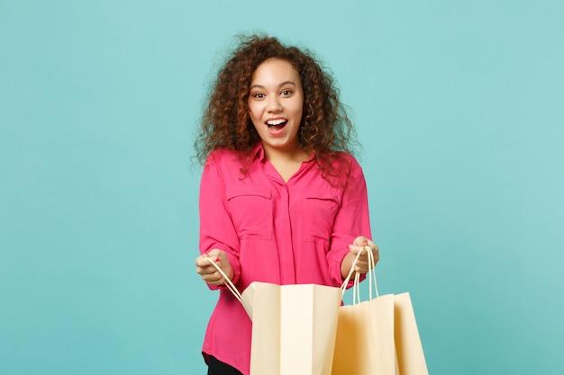 Zabawna dziewczyna afryki w różowe ubrania dorywczo trzymając pakiet torba z zakupów po zakupach na białym tle na tle niebieskiej ściany turkus. koncepcja życia szczere emocje ludzi. makieta miejsca na kopię.