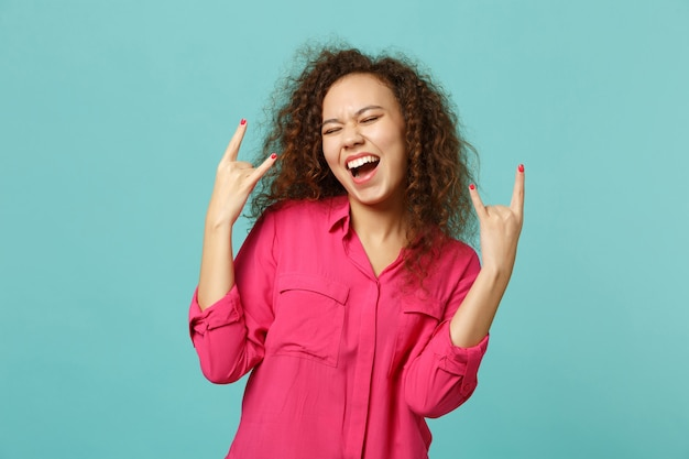 Zabawna dziewczyna afryki w różowe ubrania dorywczo, trzymając zamknięte oczy, pokazując rogi do góry gest na białym tle na niebieskim tle turkusu w studio. koncepcja życia szczere emocje ludzi. makieta miejsca na kopię.