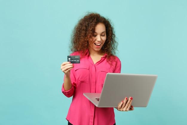 Zabawna dziewczyna afryki w ubranie przy użyciu komputera typu laptop pc, trzymając kartę kredytową bankową na białym tle na niebieskim tle turkus w studio. koncepcja życia szczere emocje ludzi. makieta miejsca na kopię.