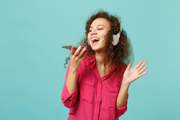 Zabawna dziewczyna afryki w ubranie trzymać telefon komórkowy, słuchanie muzyki w słuchawkach na białym tle na niebieskim tle turkusu w studio. ludzie szczere emocje, koncepcja stylu życia. makieta miejsca na kopię.
