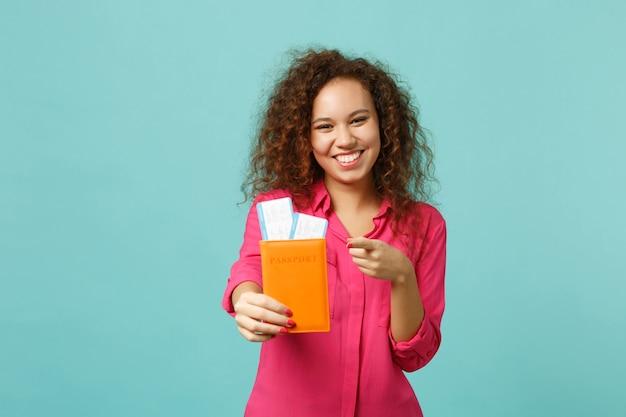 Zabawna dziewczyna afryki, wskazując palcem wskazującym na aparat trzymając bilet na kartę pokładową paszport na białym tle na niebieskim tle turkus w studio. koncepcja życia szczere emocje ludzi. makieta miejsca na kopię.