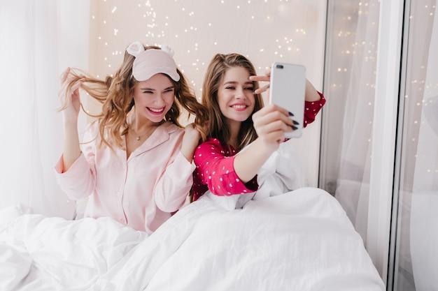 Zabawna dziewczyna bawi się kręconymi włosami w łóżku. sympatyczny kaukaski modelka co selfie rano.