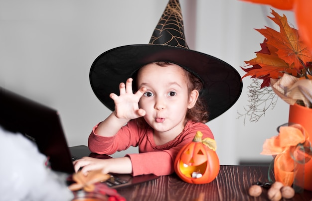 Zabawna dziewczyna dziecko w stroju czarownicy na halloween za pomocą notebooka laptopa cyfrowego tabletu. zadzwoń online do znajomych lub rodziców.