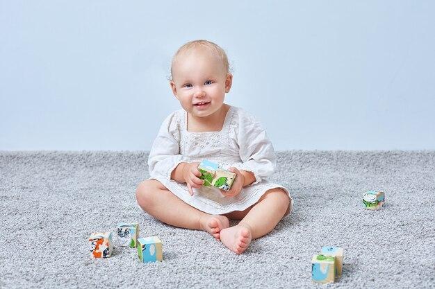 Zabawna dziewczyna gra drewniane kostki na dywanie. skopiuj miejsce.