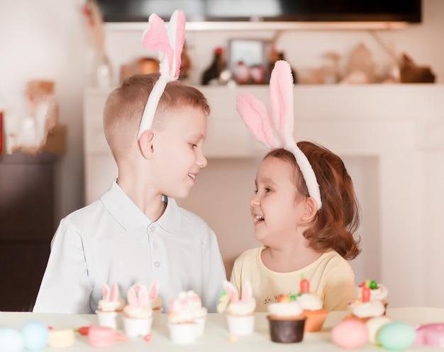Zabawna dziewczyna i chłopiec dziecko sobie uszy królika na wiosnę w domu.