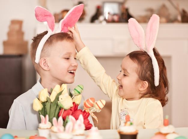 Zabawna dziewczyna i chłopiec dziecko sobie uszy królika w okresie wiosennym w domu.