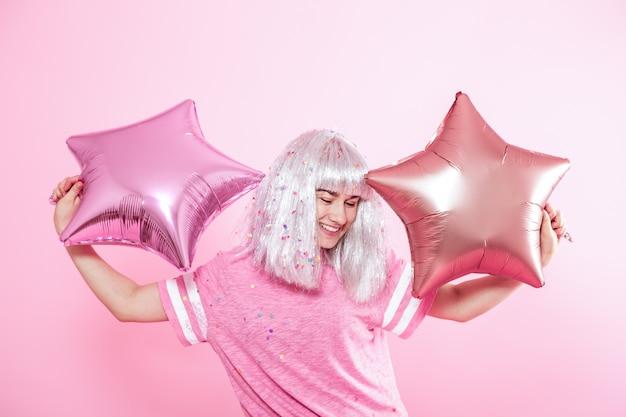 Zabawna dziewczyna o srebrnych włosach daje uśmiech i emocje. młoda kobieta lub nastolatka z balonów i konfetti