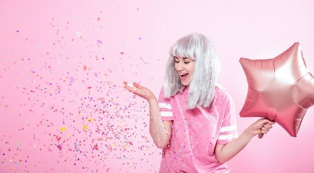 Zabawna dziewczyna o srebrnych włosach daje uśmiech i emocje na różowej ścianie. młoda kobieta lub nastolatka z balonów i konfetti