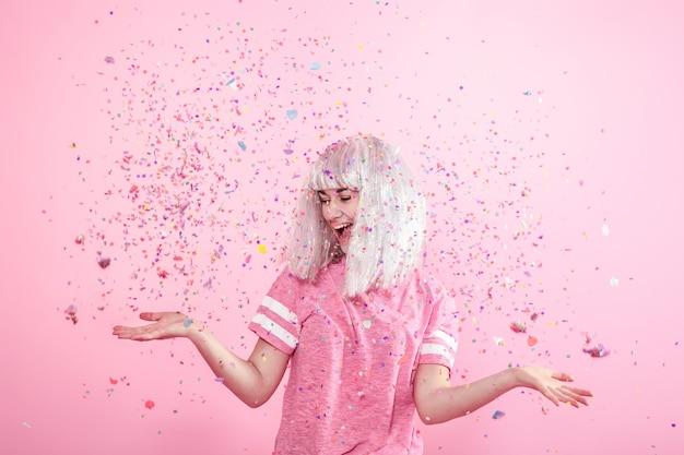 Zabawna dziewczyna o srebrnych włosach daje uśmiech i emocje na różowej ścianie. młoda kobieta lub nastolatka z konfetti