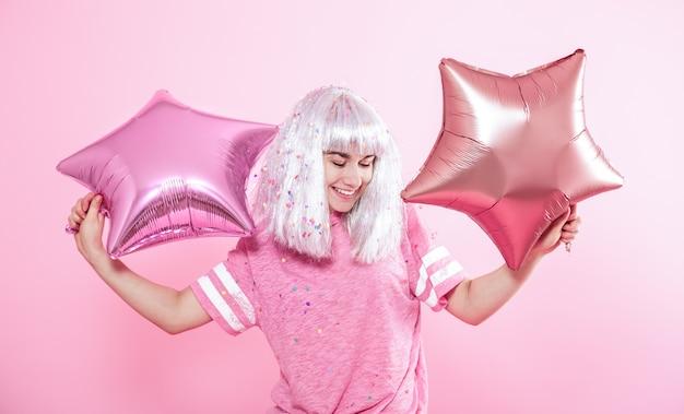 Zabawna dziewczyna o srebrnych włosach daje uśmiech i emocje na różowym tle. młoda kobieta lub nastolatka z balonów i konfetti