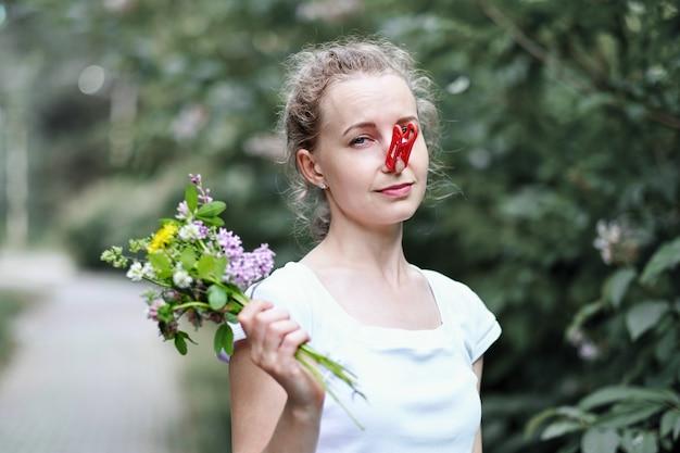 Zabawna dziewczyna próbuje desperacko walczyć z wiosenną alergią na kwiaty. kobieta chroniąca nos przed alergenami za pomocą spinacza do bielizny