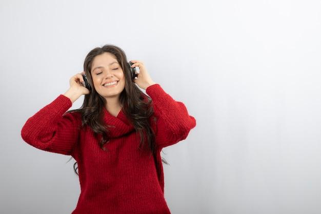 Zabawna dziewczyna słucha muzyki w słuchawkach.