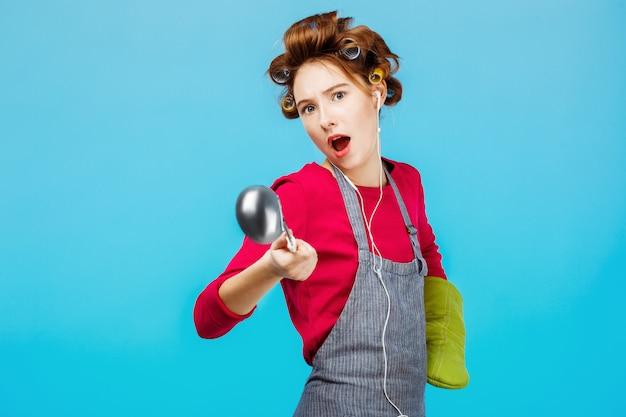 Zabawna dziewczyna tańczy podczas gotowania obiadu z zieloną rękawiczką na rękę