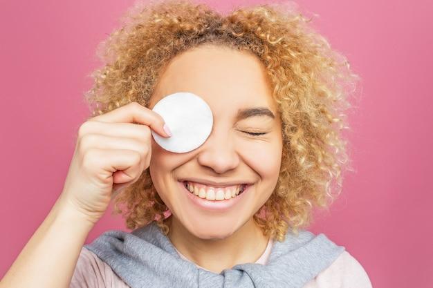 Zabawna dziewczyna trzyma małą białą gąbkę na oku i uśmiecha się.