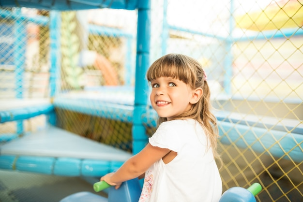 Zabawna dziewczyna w białej sukni w centrum rozrywki dla dzieci uśmiecha się i patrzy na kamery