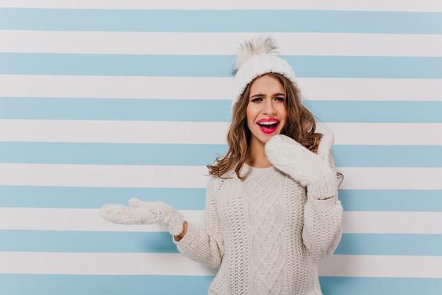 Zabawna dziewczyna w ciepłej czapce i zimowym swetrze robi zdziwioną minę. słowiańska modelka pozuje do portretu