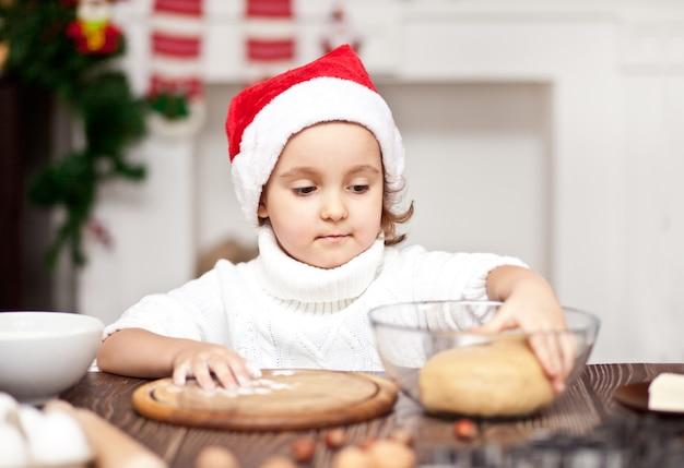 Zabawna dziewczyna w czapce mikołaja pieczenia ciasteczek świątecznych w domu.