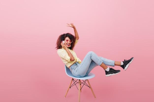 Zabawna dziewczyna w czarnych trampkach i białych skarpetkach pozuje z różowym wnętrzem i słucha ulubionej piosenki. urocza afrykańska kobieta w modnych dżinsach siedzi na krześle.