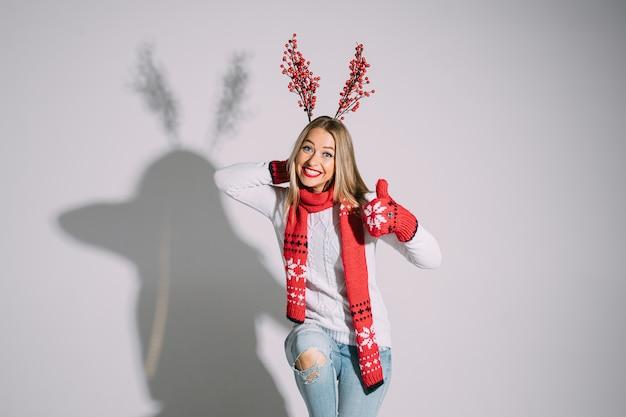 Zabawna dziewczyna w czerwonym zimowym szaliku i rękawiczkach pokazuje kciuk do góry i uśmiecha się z gałęziami czerwonych jagód za głową, robiąc rogi renifera.