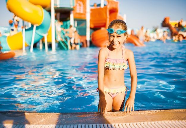 Zabawna dziewczyna w niebieskich okularach do pływania stoi w basenie z czystą przezroczystą wodą, patrząc w kamerę i ciesząc się ciepłym letnim słońcem