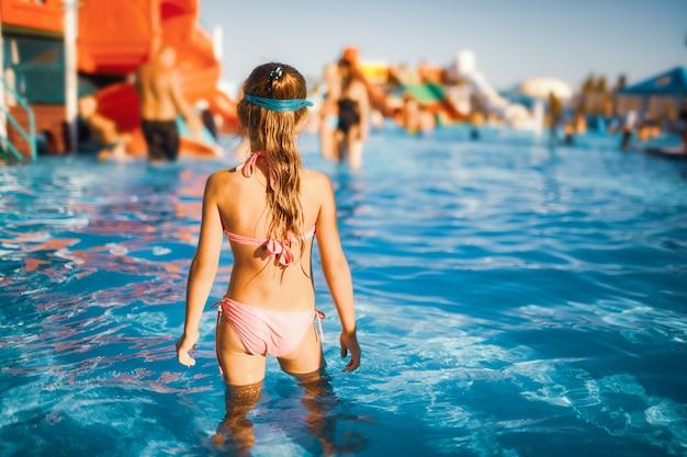 Zabawna dziewczyna w niebieskich okularach do pływania stoi w basenie z przejrzystą, przezroczystą wodą, ciesząc się ciepłym letnim słońcem