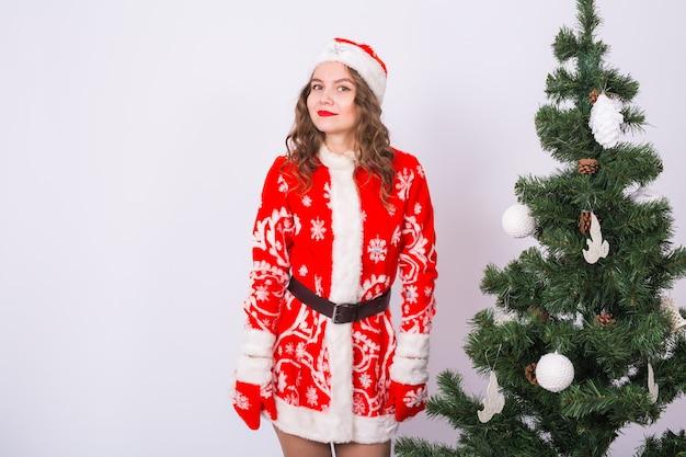 Zabawna dziewczyna w noszeniu świątecznego stroju świętego mikołaja w pobliżu choinki.