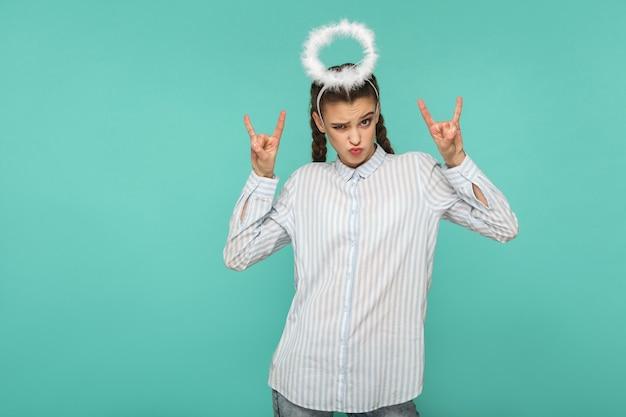 Zabawna dziewczyna w pasiastą niebieską koszulę i fryzurę warkocz, stojąc z aureolą na głowie i patrząc na kamery ze znakiem rocka i pocałunkiem, strzał w studio, na białym tle na niebieskim lub zielonym tle